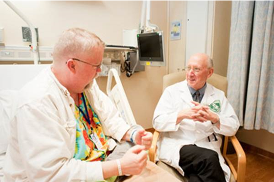Dr. Steven A. Rosenberg speaking with a patient at the NIH Clinical Center.