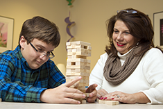 Child and Caregiver play Jenga together