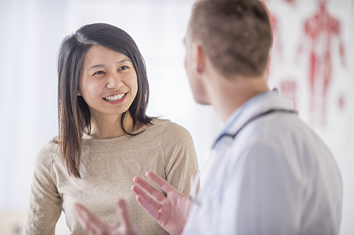 Woman smiling in conversation with her doctor