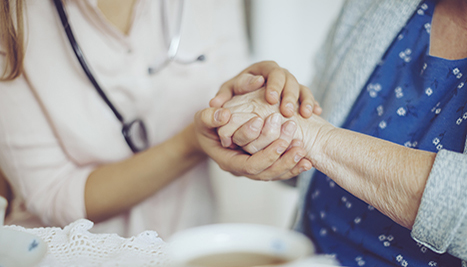 Social worker holding patient's hand