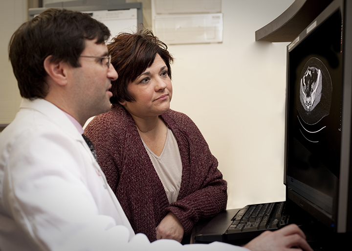 Photo of Arrica Wallace and Christian Hinrichs, M.D., discussing her scans