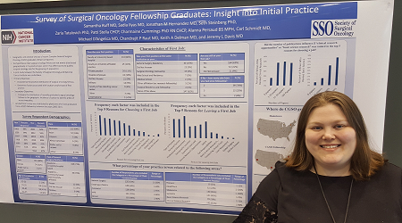 A clinical fellow standing in front of her research poster
